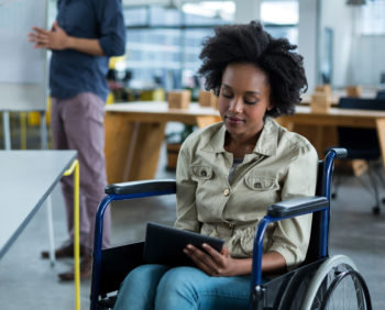 Disabled business executive in wheelchair using digital tablet in office